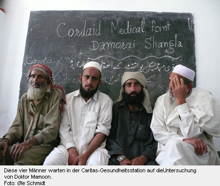 Diese vier Männer warten in der Caritas-Gesundheitsstation auf die Untersuchung von Doktor Mamoon.