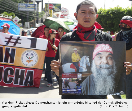 Auf dem Plakat dieses Demonstranten ist ein ermordetes Mitglied der Demokratiebewegung abgelichtet